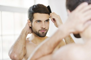 Morning routine. Rear view of handsome young beard man combing h