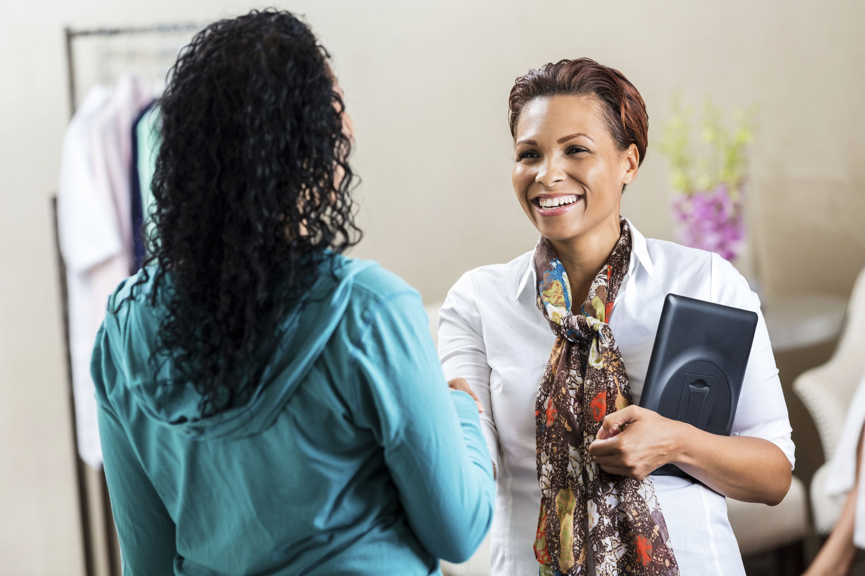 Professional woman greeting customer or client in upscale lobby