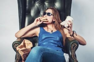 Funny crazy woman eating hamburger junk food and fries sitting