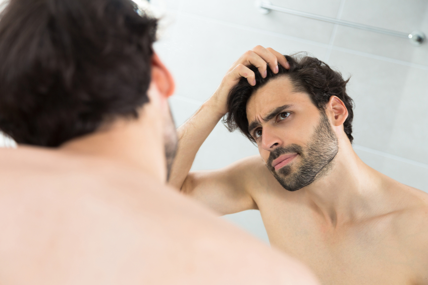 Caucasian adult man checking hairline.Hair loss problems