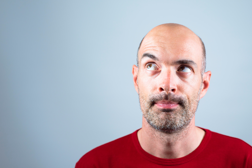 Male portrait, guy making a funny face while thinking. Horizontal framing.