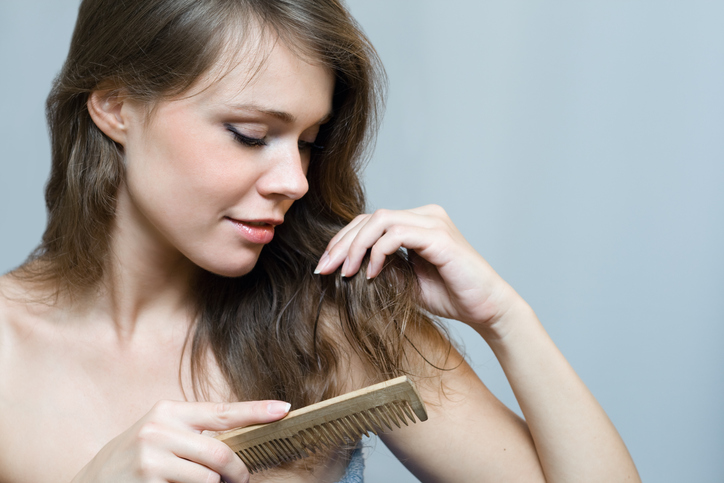 Naked woman combing her long hair with a comb