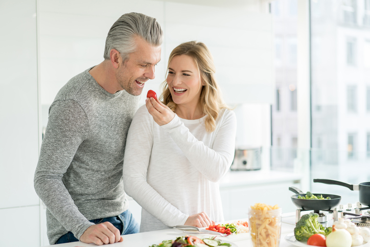 Happy couple cooking at home