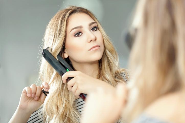 Beautiful woman straightening her hair