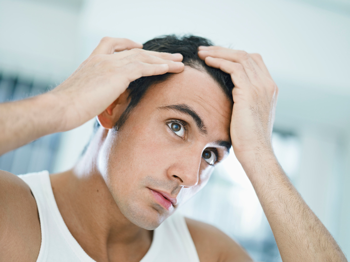 caucasian adult man checking hairline. Horizontal shape, head and shoulders, front view