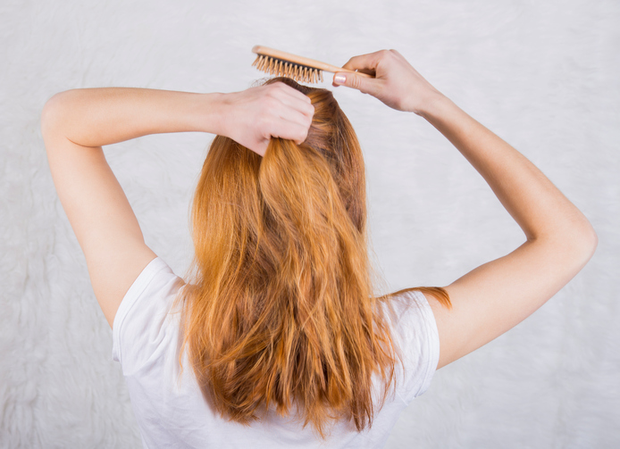 Red-haired young woman combing hair with wooden comb.