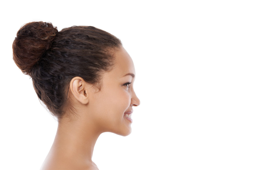 side view of a woman with her curly, dark hair pulled into a ballerina bun