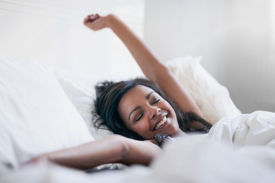 happy african american woman waking up bed beauty rest 2020 new year beauty resolutions toppik hair blog