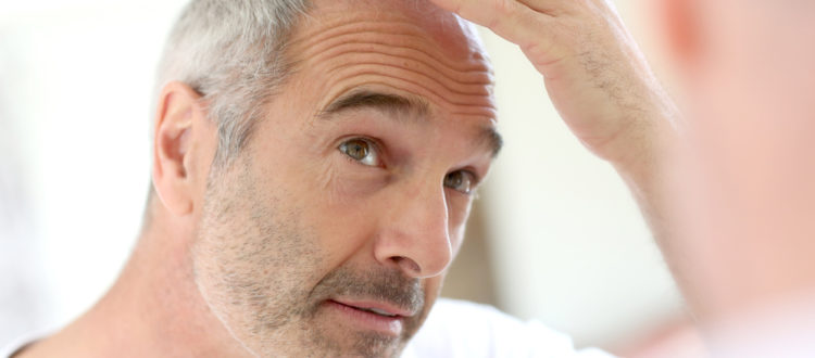 man-gray-hair-examine-receding-hairline-mirror-male-pattern-baldness-toppik-blog