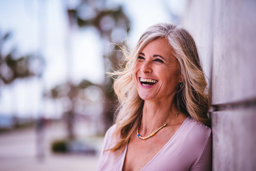 smiling happy woman long gray hair causes gray hair toppik blog post