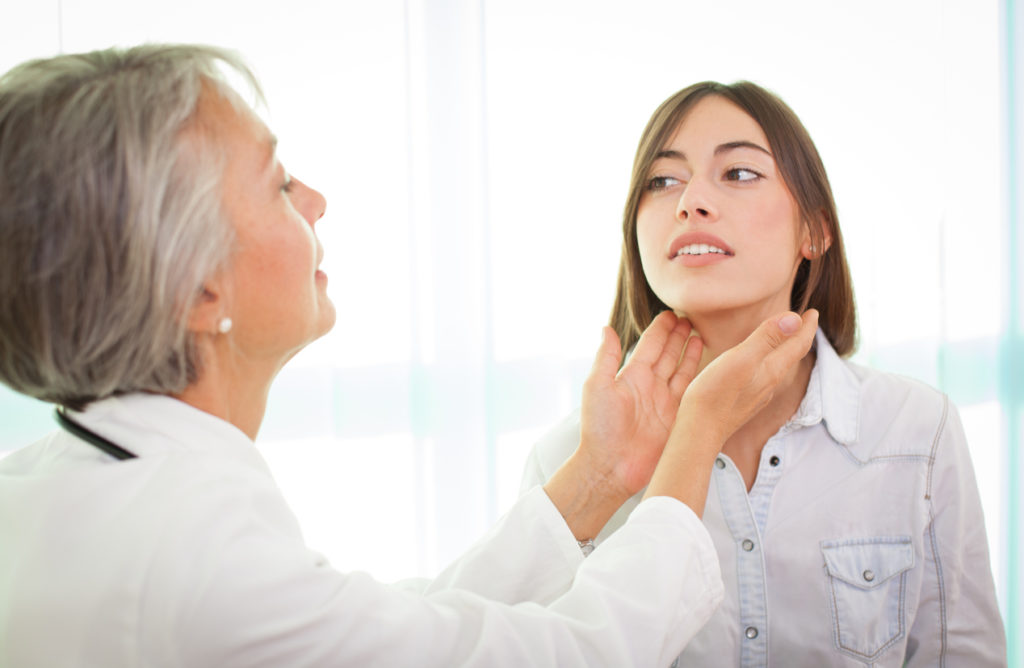 Doctor examines young female patient's thyroid hypothyroidism hair loss Toppik hair blog
