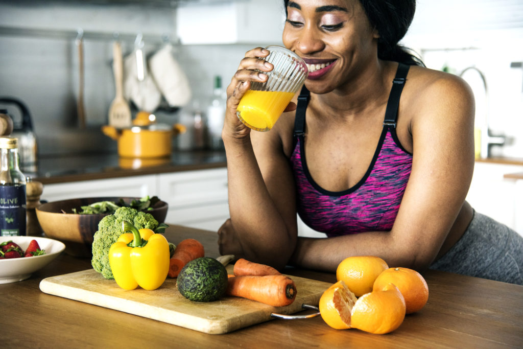 Black woman drinking orange juice healthy diet maintaining healthy hair follicle function toppik hair blog