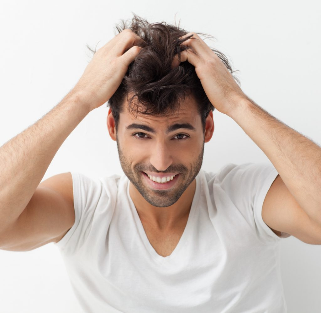man smiling scratching scalp hair dry hair when is hair conditioner for men necessary?