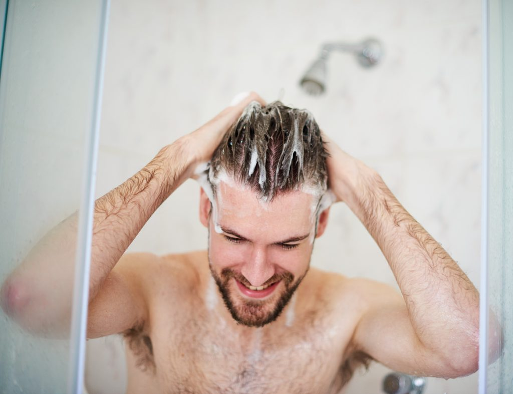 Man conditions his hair as part of his 2020 New Year Beauty Resolutions