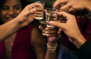 drinks shots toasting in bar the link between alcohol and hair loss toppik hair blog