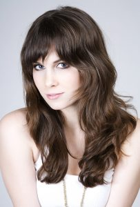 brunette woman bangs fringe white shirt wavy hair with bangs our favorite wavy hairstyles toppik hair blog