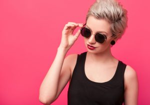 blonde short hair sunglasses red background textured pixie haircut our favorite wavy hairstyles toppik hair blog
