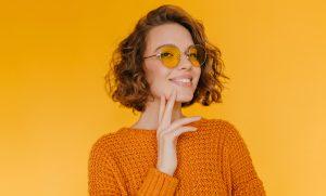 orange background woman smiling curly hair short chin length wavy bob our favorite wavy hairstyles toppik hair blog