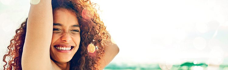smiling woman curly hair arms up beach summer how to deal with humidity hair toppik hair blog