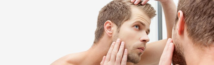 man examine thin hair hairline bald spot in mirror knowing your bald spot treatment options toppik hair blog