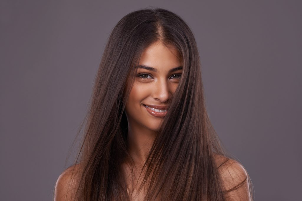 smiling happy woman long hair brunette can caffeine help hair growth toppik hair blog