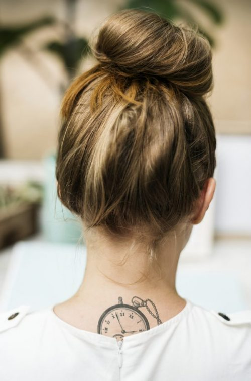 Rear view woman tattoo messy top knot hair bun our favorite bun hairstyles toppik hair blog