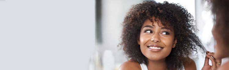 woman smiling mirror african american natural curly hair understanding the anatomy of hair toppik hair blog