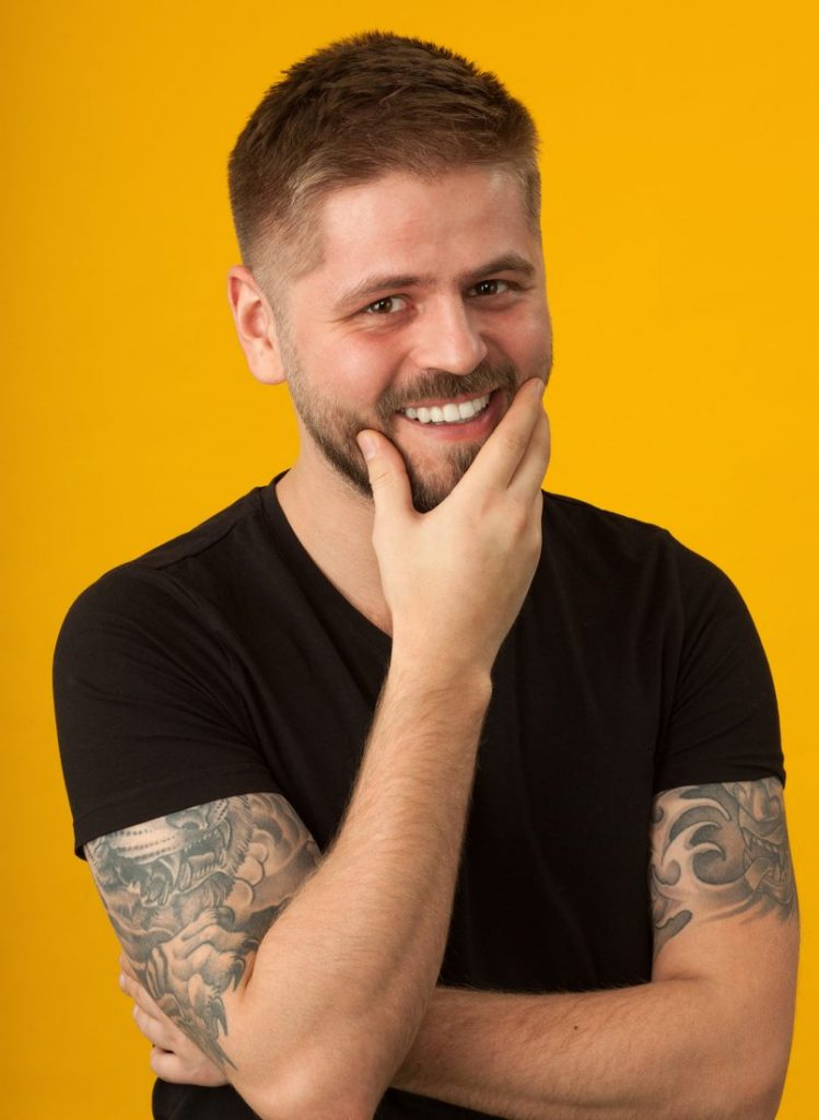 smiling man orange background tattoos high and tight  hairstyle our favorite short haircuts for men toppik hair blog