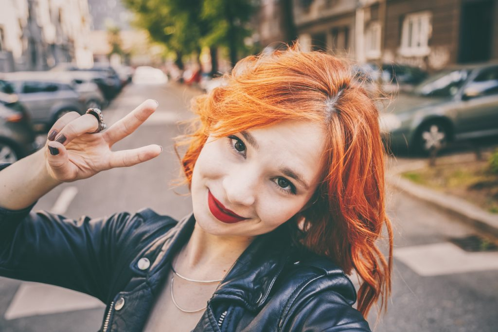 woman selfie peace sign golden copper hair color fall hair color trends toppik hair blog