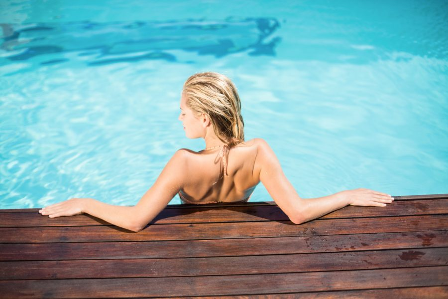 woman swimming pool back deck wet hair after swimming care for thinning hair toppik hair blog