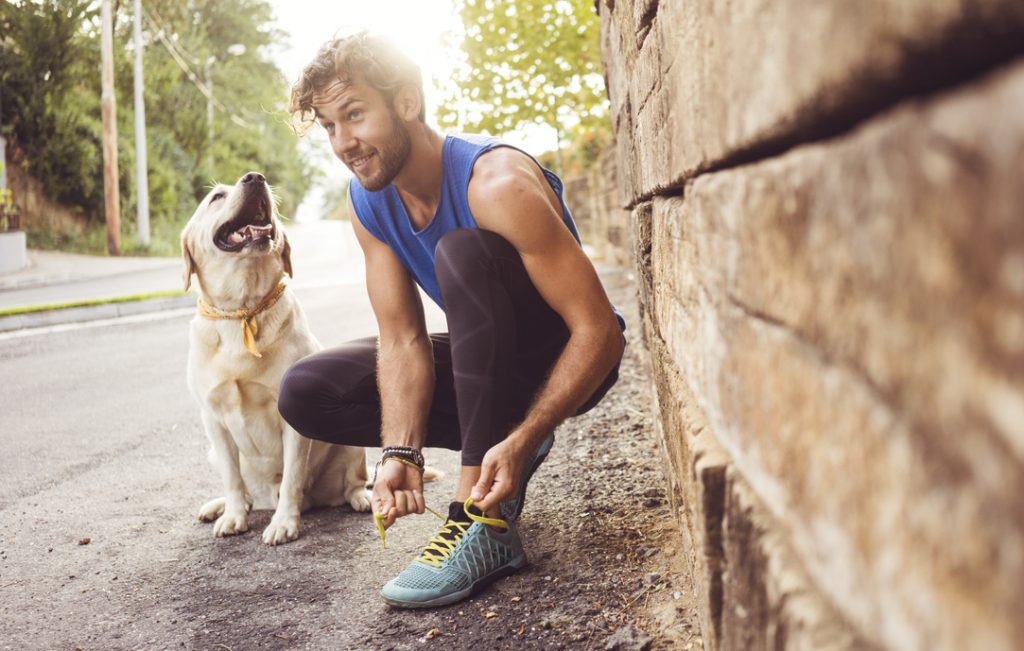 man with a beard exercising outside on road with dog how to get a thicker beard toppik hair blog