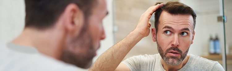 A man styles his hair in the mirror. How to add volume to thin hair.