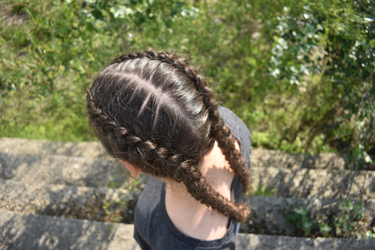Woman outside, pictured from above with two dutch braids. Stop hair shedding now, toppik hair blog