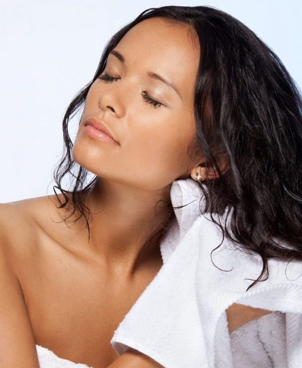 woman drying wet hair with towel. protect hair while sleeping toppik hair blog