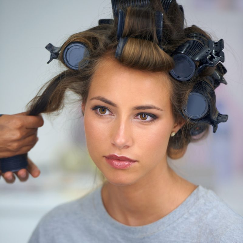 A woman in a gray shirt gets large, volumizing curlers taken out of her hair.