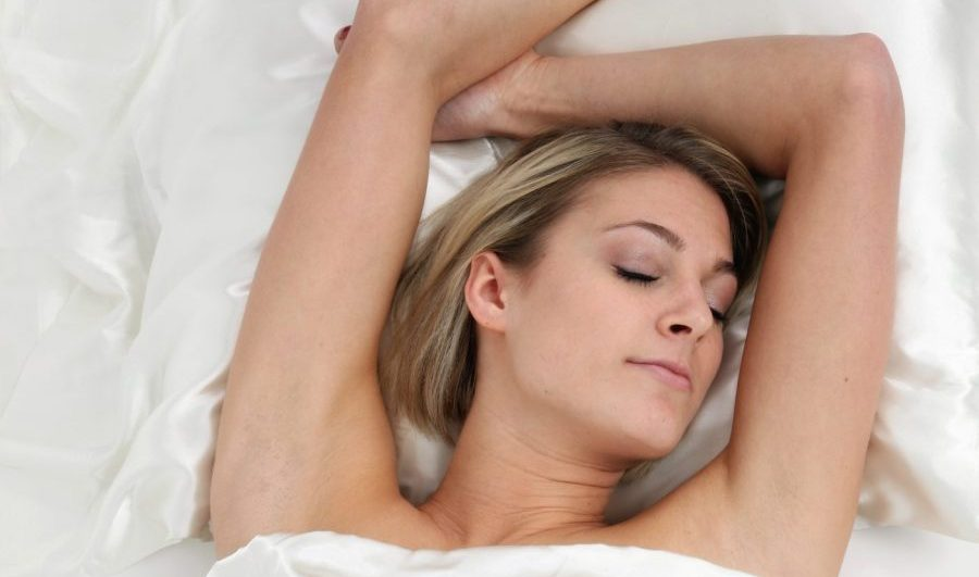 blonde woman sleeping on a white silk pillowcase and sheets. protect hair while sleeping toppik hair blog