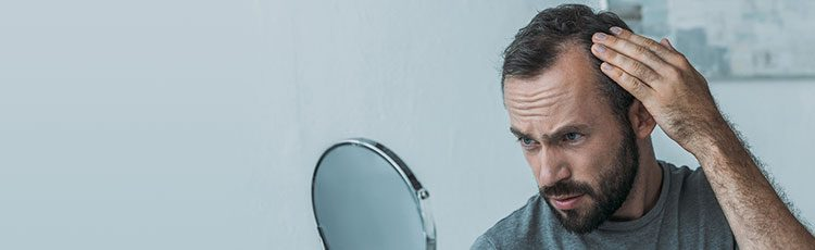 man examining receding hairline balding in mirror are you balding? toppik hair blog