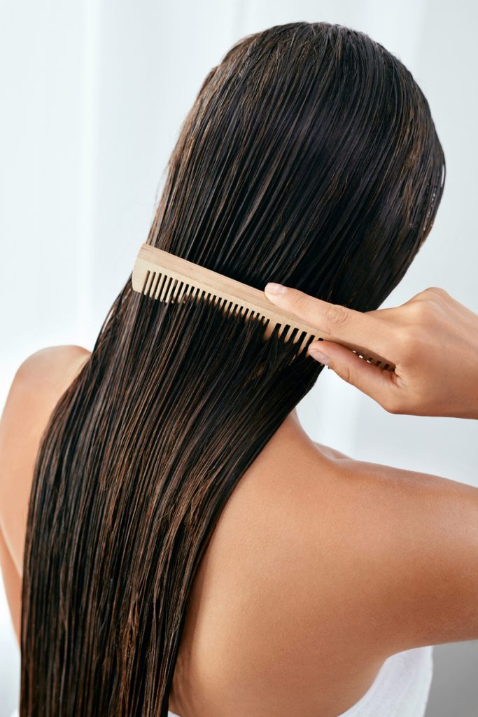 woman back combing wet hair long brown hair after bath shampooing white towel wood comb the best shampoo for hair growth and thickening toppik hair blog