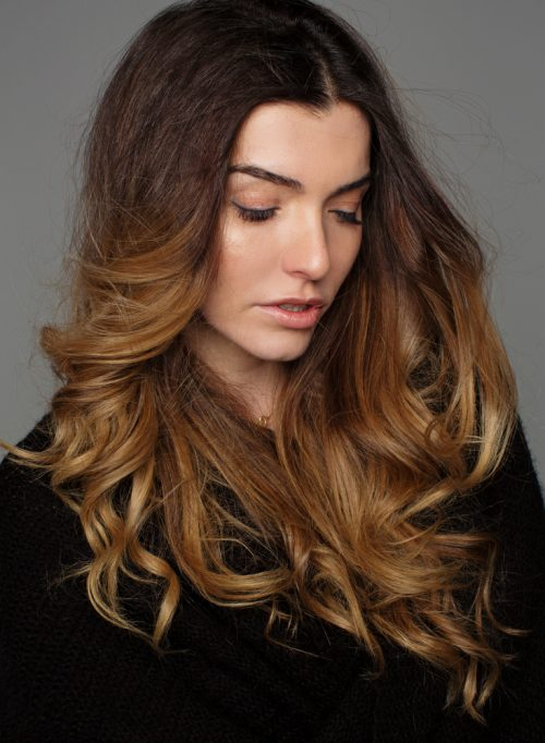 woman long wavy hair sombre hair color highlights looking down - What is sombre hair?