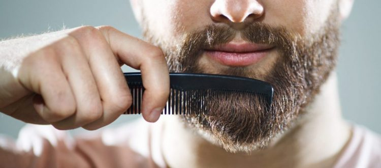closeup man combing his beard mustache styles for movember no-shave november toppik hair blog