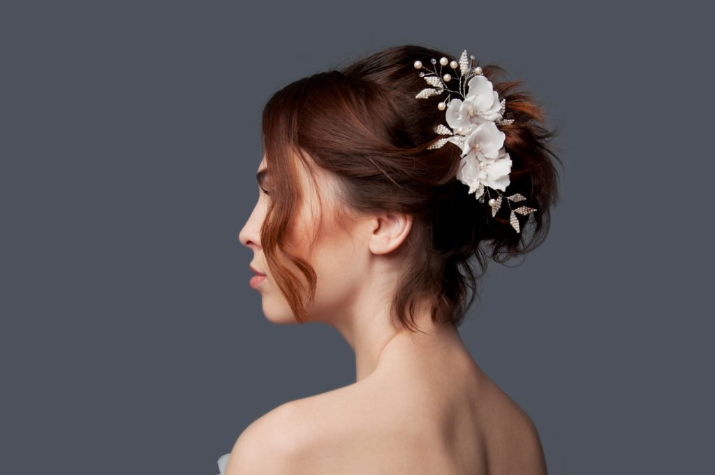 Side view of a bride, her dark brown hair twisted in an updo, accented by white silk bead pearl flowers for her wedding day.