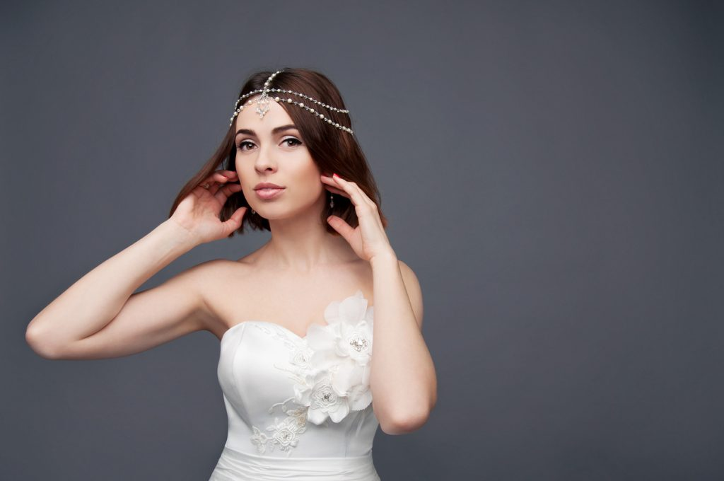 A bride with thin brown hair wears it in a short bob wedding hairstyle, accented nicely by a multi-strand pearl headband.