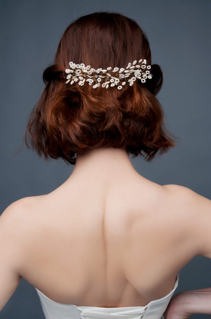 Back view of a bride with a short wedding hairstyle, half pulled back in a beaded clip.