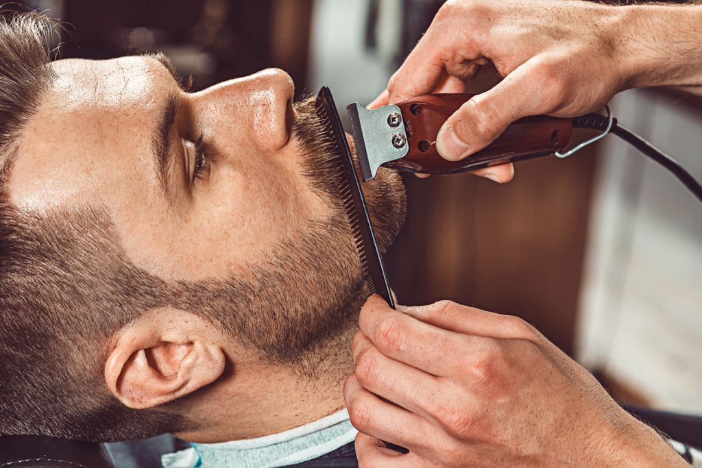 Man in barber shop gets beard trimmed and combed for movember or no-shave november challenge.