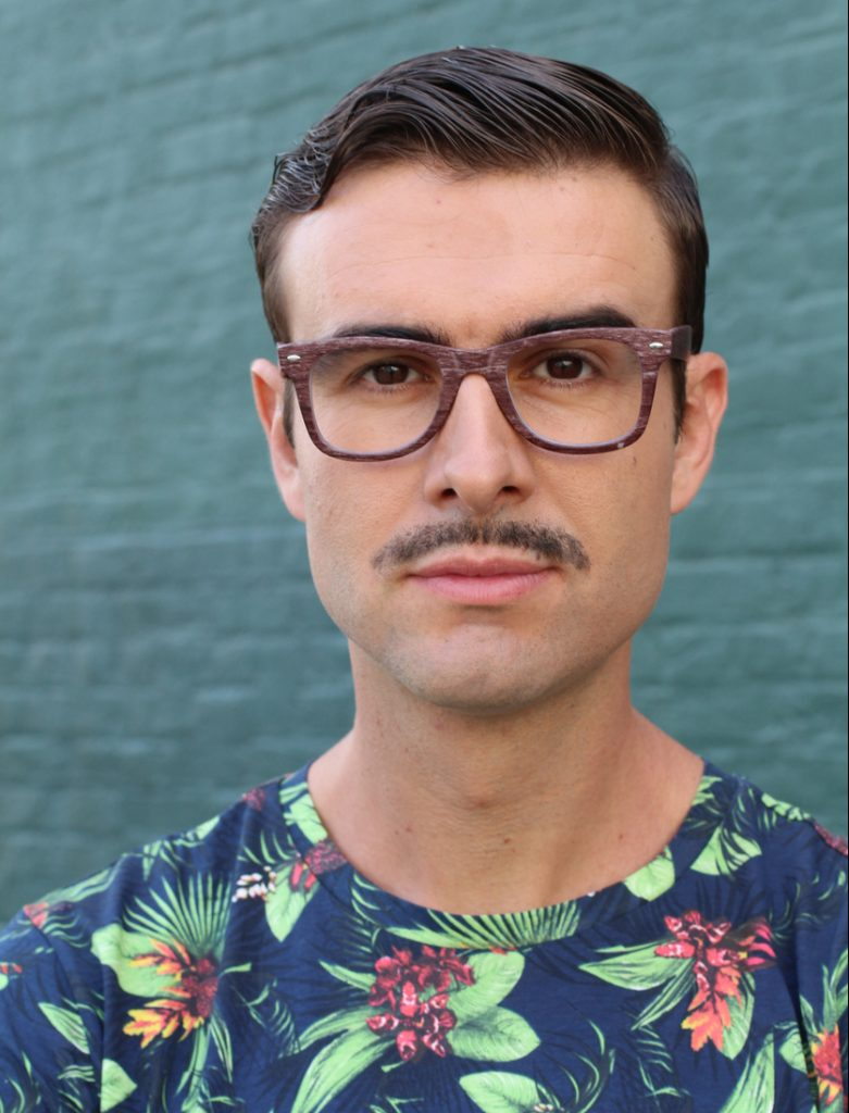 A pencil mustached man wears dark hair glasses and a floral shirt. Perhaps he is participating in movember.