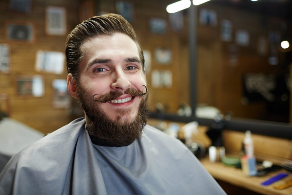 A smiling man sits in a barber shop chair, his handlebar mustache curls up at both corners and his beard is full.