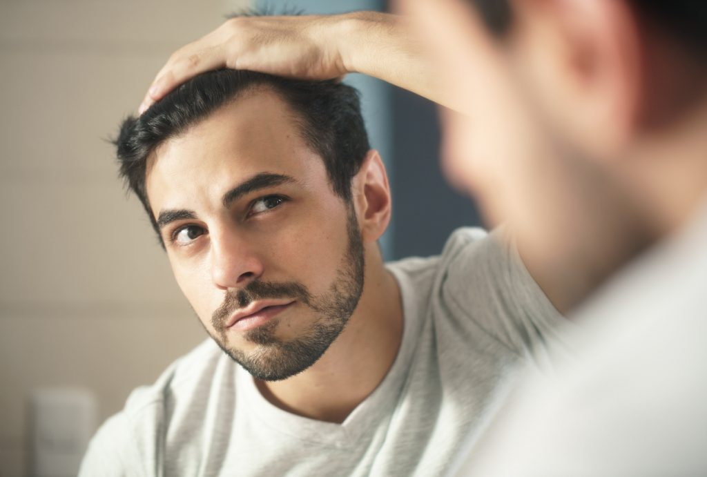 man examining receding hairline in mirror dark brown hair are you balding? toppik hair blog