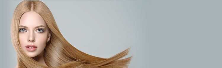closeup woman long shiny blonde hair blowing side gray background haircuts for long thin hair toppik hair blog