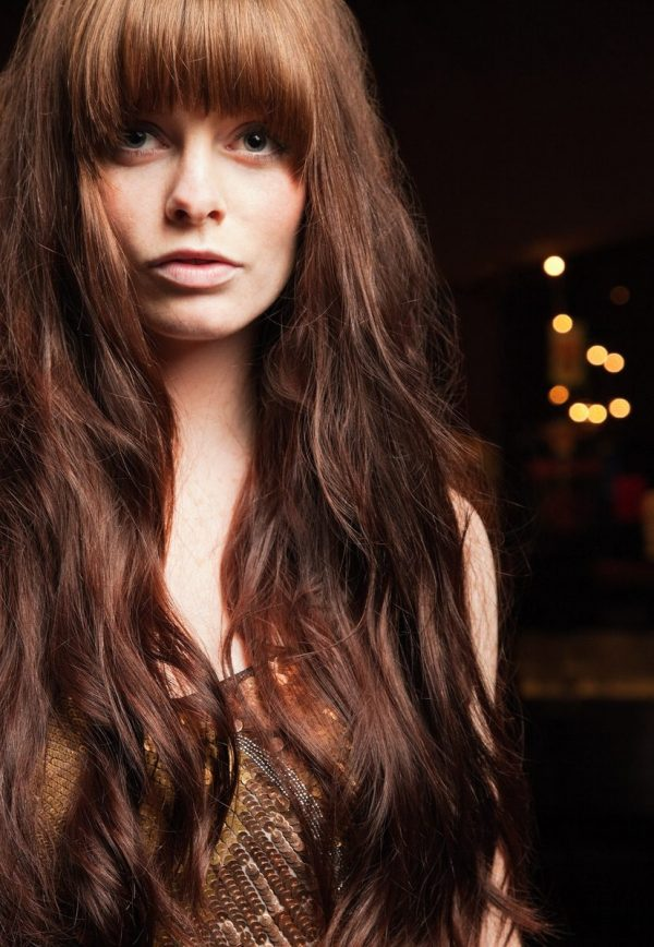 Closeup woman red auburn long hair bangs dark black background brown sequin shirt haircuts for long thin hair toppik hair blog