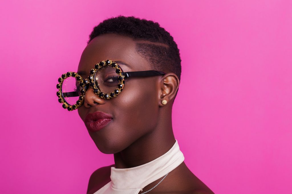african american woman short shaved hair part jeweled glasses pink background shaved hair designs for thin hair toppik hair blog